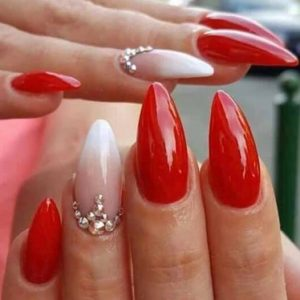 pointed nail extensions with red shellac colour on top and gems